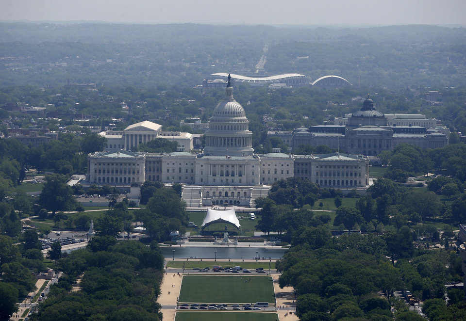 Photo - RFK Memorial Stadium is visible behind the U.S. Capitol from the 500-foot level of the Washington Monument in Washington, Monday, May 12, 2014, as it re-opens. The monument, which sustained damage from an earthquake in August 2011, reopened to the public today. (AP Photo)