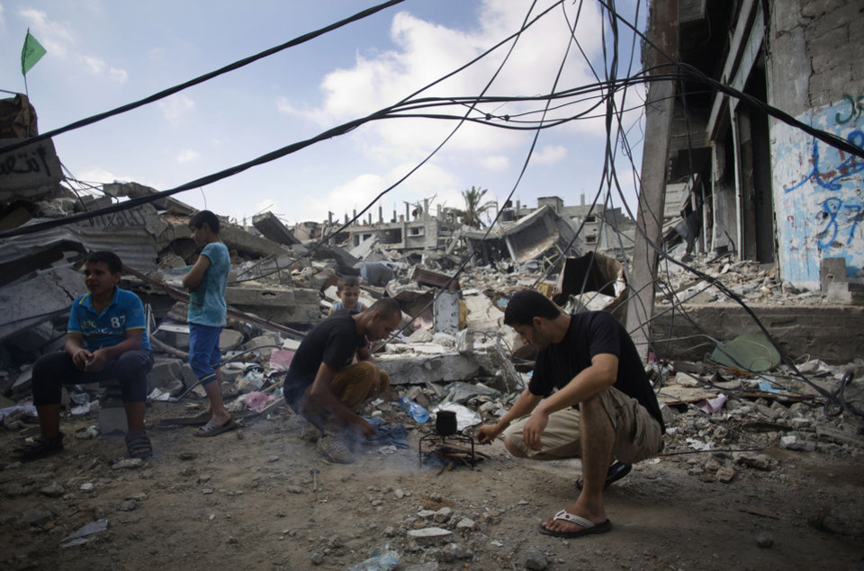 Photo - Palestinians make coffee next to their destroyed house in Gaza City's Shijaiyah neighborhood, Wednesday, Aug. 27, 2014.  The third Gaza War in six years appears to have ended in another sort of tie, with both Israel and Hamas claiming the upper hand. Their questionable achievements have come at a big price, especially to long-suffering Palestinians in Gaza.  (AP Photo/Khalil Hamra)