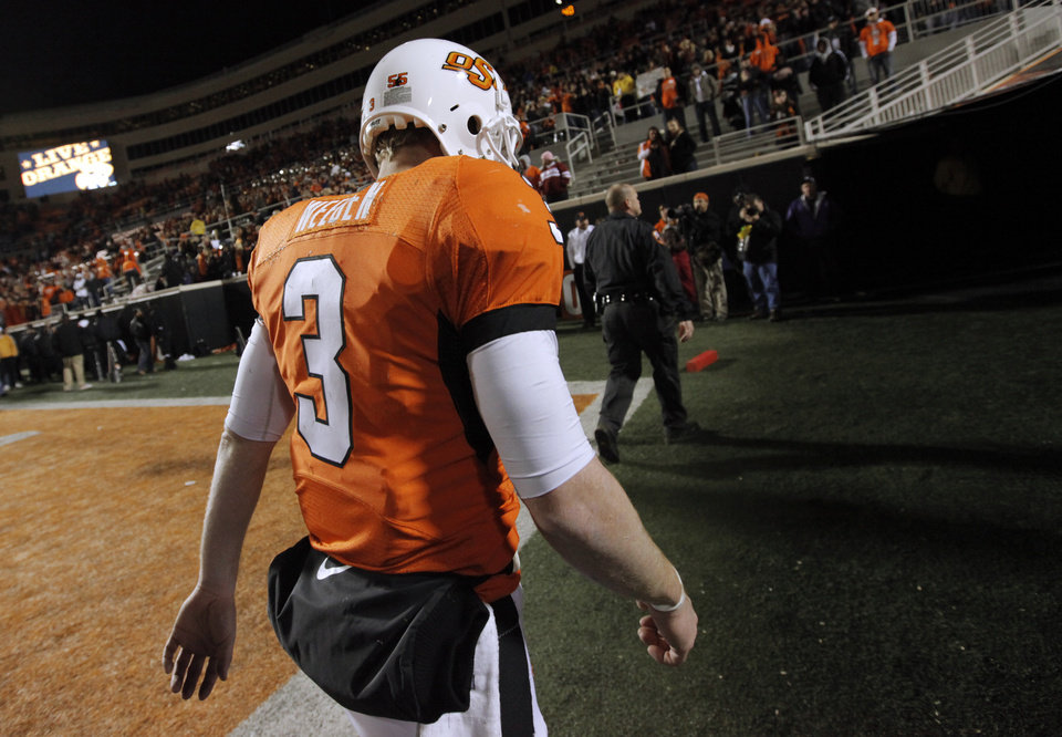 Photo - OSU quarterback Brandon Weeden (3) leaves the field after the Bedlam college football game between the University of Oklahoma Sooners (OU) and the Oklahoma State University Cowboys (OSU) at Boone Pickens Stadium in Stillwater, Okla., Saturday, Nov. 27, 2010. OU won, 47-41. Photo by Nate Billings, The Oklahoman