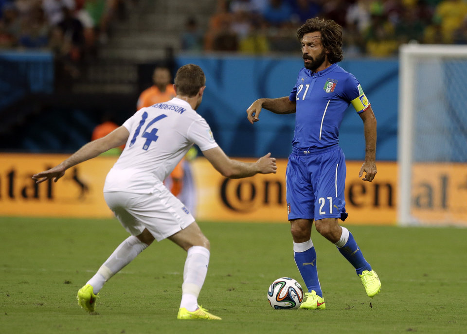 Photo - England's Jordan Henderson, left, closes down Italy's Andrea Pirlo during the group D World Cup soccer match between England and Italy at the Arena da Amazonia in Manaus, Brazil, Saturday, June 14, 2014.  (AP Photo/Matt Dunham)