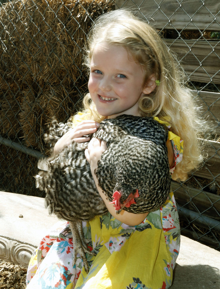 Photo -  Katherine McCoy, 4, plays with chickens in the backyard garden of Sara and David Braden. Sara Braden is one of the organizers of the urban farm and garden tour. Photo by Paul Hellstern, The Oklahoman   PAUL HELLSTERN -