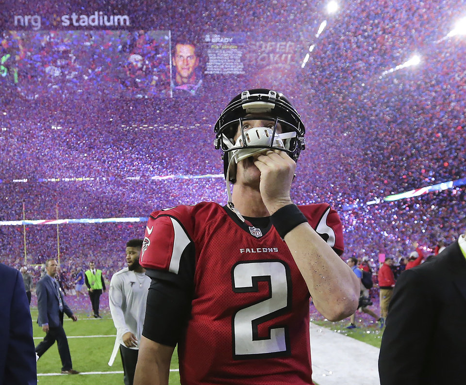 Photo - In this photo taken Feb. 5, 2017, Atlanta Falcons quarterback Matt Ryan reacts after losing Super Bowl 51 as the screen flashes New England Patriots quarterback Tom Brady and confetti flies in Houston. (Curtis Compton/Atlanta Journal-Constitution via AP)