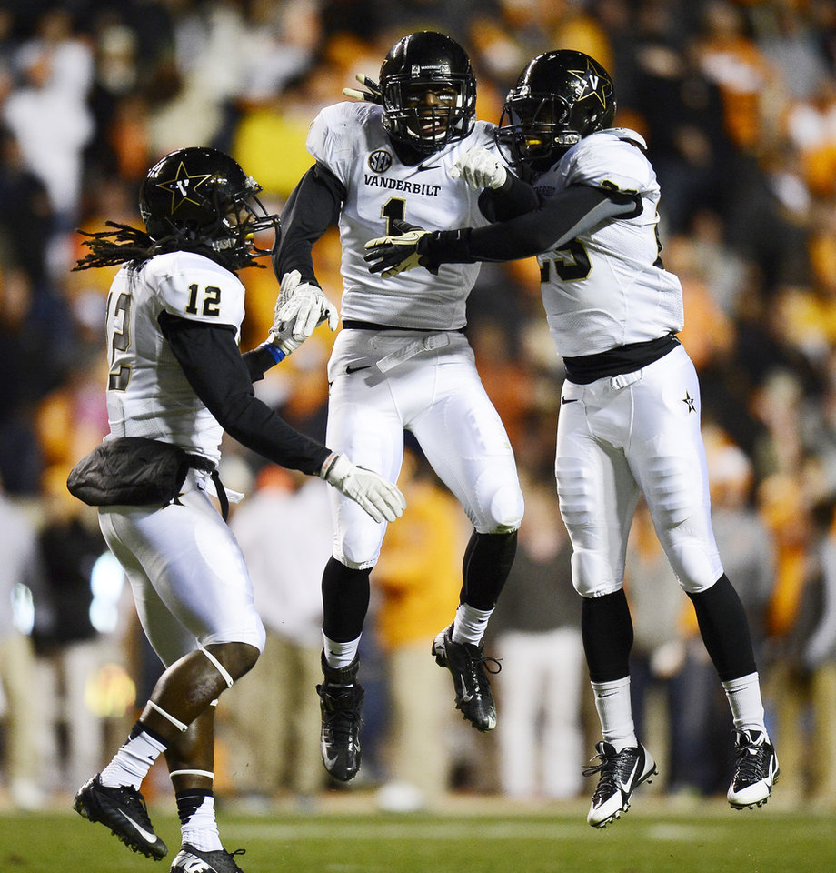 Photo - Vanderbilt safety Kenny Ladler (1) celebrates with defensive backs Steven Clarke (12) and Andre Hal (23) after intercepting a pass against Tennessee in the first quarter of an NCAA college football game on Saturday, Nov. 23, 2013, in Knoxville, Tenn. (AP Photo/Mark Zaleski)