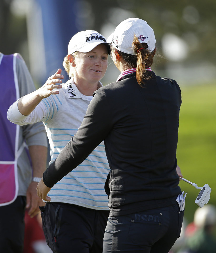 Photo - Stacy Lewis, left, greets Lydia Ko, right, of New Zealand on the 18th green of the Lake Merced Golf Club after the final round of the Swinging Skirts LPGA Classic golf tournament on Sunday, April 27, 2014, in Daly City, Calif. Ko won the event after shooting a 3-under-par 69 to finish at 12-under-par and Lewis finished second. (AP Photo/Eric Risberg)