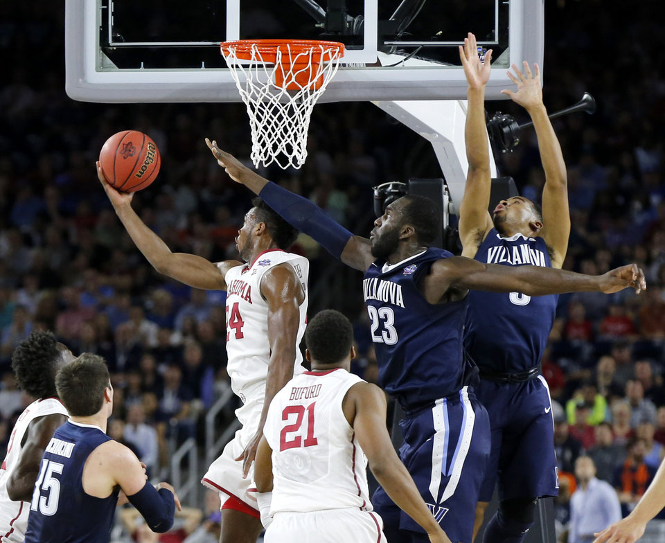 Photo - Oklahoma's Buddy Hield (24) goes past Villanova's Daniel Ochefu (23) and Phil Booth (5) during the national semifinal between the Oklahoma Sooners (OU) and the Villanova Wildcats in the Final Four of the NCAA Men's Basketball Championship at NRG Stadium in Houston, Saturday, April 2, 2016. Photo by Nate Billings, The Oklahoman