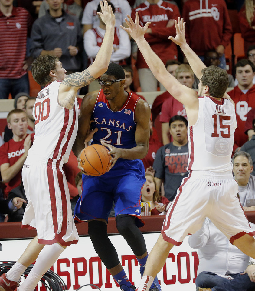 Photo - Oklahoma's Ryan Spangler (00) and Tyler Neal (15) try to defend on Kansas' Joel Embiid (21) during the NCAA college basketball game between the University of Oklahoma Sooners (OU) and the University of Kansas (KU) Jayhawks at Lloyd Nobel Center in Norman,  Okla. on Wednesday, Jan. 8, 2014.   .Photo by Chris Landsberger, The Oklahoman