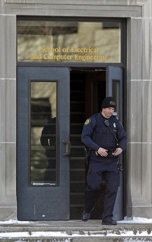 Photo - A police officer walks out of the Electrical Engineering Building on the campus of Purdue University in West Lafayette, Ind., Tuesday, Jan. 21, 2014 where  one person was killed inside a classroom by a gunman who surrendered to a police officer within minutes of the attack, officials said.. (AP Photo/Michael Conroy)