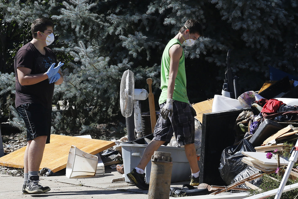 Photo - Boys wear masks and gloves as they walk among destroyed household items several days after massive flooding swept through Longmont, Colo., Wednesday Sept. 18, 2013. As water recedes and flows east onto the Colorado plains, rescuers are shifting their focus from emergency airlifts to trying to find the hundreds of people still unaccounted for after last week's devastating flooding. (AP Photo/Brennan Linsley)
