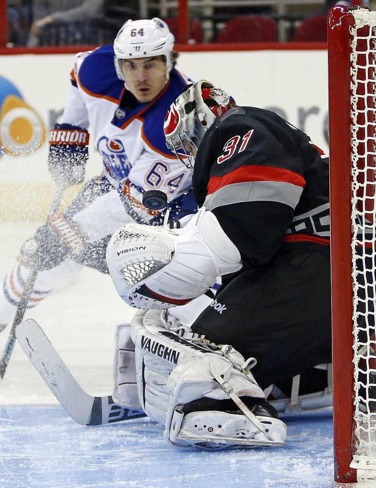 Photo - Edmonton Oilers' Nail Yakupov (64) of Russia, has his shot blocked by Carolina Hurricanes goalie Anton Khudobin (31) of Kazakhstan, during the first period of an NHL hockey game in Raleigh, N.C., Sunday, March 16, 2014. (AP Photo/Karl B DeBlaker)
