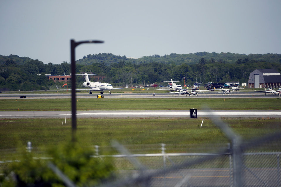 Photo - The site of a plane crash is seen in the distance, across Hanscom Field in Bedford, Mass., Sunday, June 1, 2014. The co-owner of the Philadelphia Inquirer newspaper, Lewis Katz, was killed along with six other people in a fiery plane crash in Massachusetts, just days after reaching a deal that many hoped would end months of infighting at the newspaper and help restore it to its former glory. (AP Photo/Michael Dwyer)