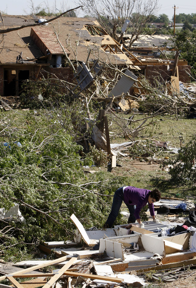 Jena Jeffcoat helps sort through debris for a neighbor in Woodward, Okla., Sunday, April 15, 2012. A tornado that killed five people struck Woodward, Okla., shortly after midnight on Sunday, April15, 2012.  Photo by Bryan Terry