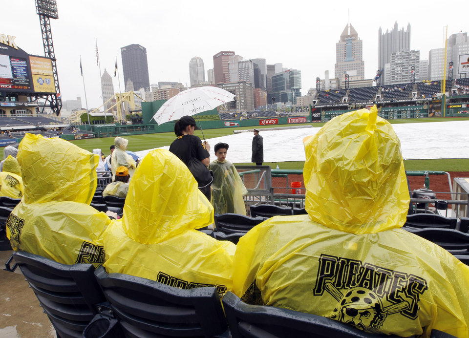Photo -   Baseball fans wear ponchos and use umbrellas while the infield tarp protects the field as it rains before the scheduled start of a baseball game between the Pittsburgh Pirates and the Houston Astros, Sunday, May 13, 2012, in Pittsburgh. (AP Photo/Keith Srakocic)