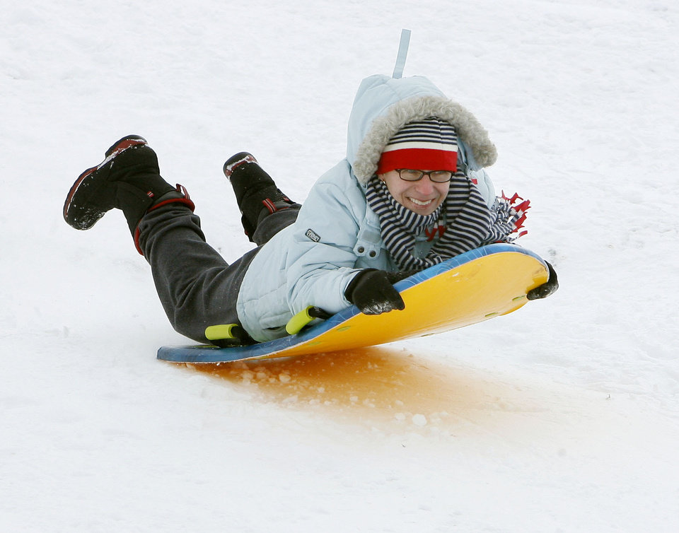 Photo - Jo Baroli flies over a bump as she sleds at Will Rogers Park in Oklahoma City, Saturday, Jan. 30, 2010. By Paul Hellstern, The Oklahoman