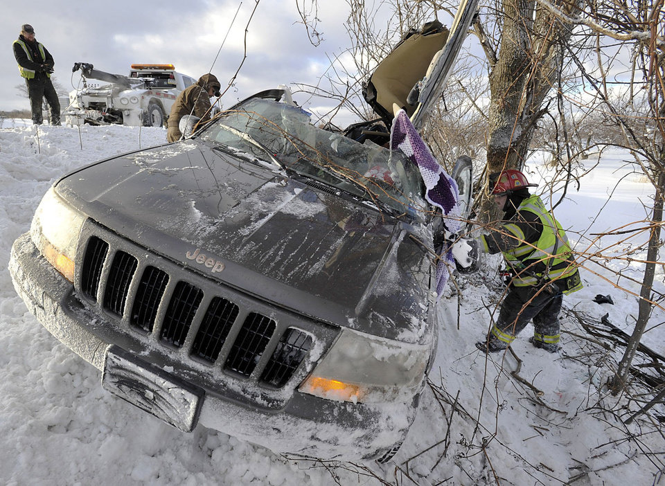Photo - Tow operators work to salvage a wrecked Jeep as Fuller Hose Co. Lt. Chris Skrekla, right, searches for the vehicle identification number after two people were injured in a rollover accident on westbound Interstate 90 just west of the Bort Road overpass in North East Township, near Erie, Pa. on Friday, Jan. 3, 2014. Pennsylvania State Police responded to numerous accidents in the area early Friday due to wintry weather.   (AP Photo/Erie Times-News, Greg Wohlford) TV OUT; MAGS OUT