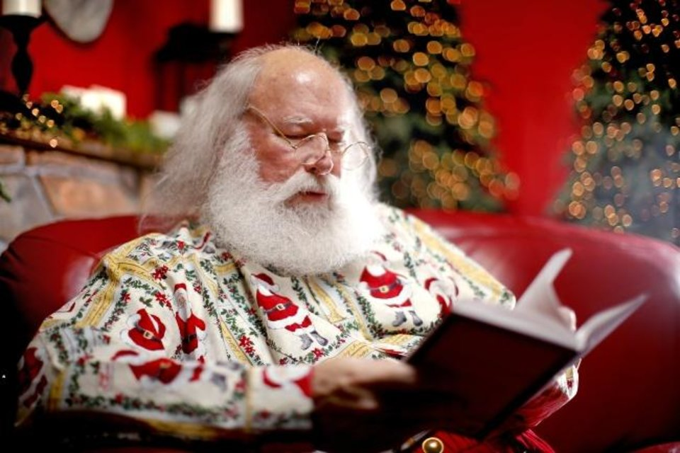 Photo -  Dan Short, who portrays Santa Claus at North Pole City, reads his new book,