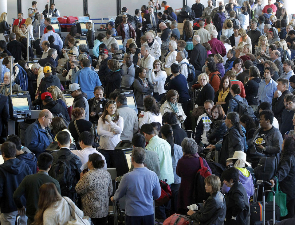 Photo - Passengers gather at the American Airlines check-in for flights at Los Angeles International Airport on Tuesday, April 16, 2013. Computer problems forced American Airlines to ground flights across the country Tuesday after the airline was unable to check passengers in and book passengers. (AP Photo/Nick Ut)