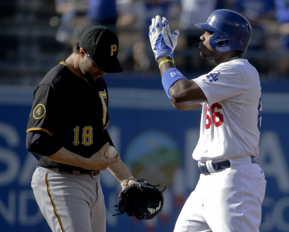 Photo - Los Angeles Dodgers' Yasiel Puig, right, celebrates after a double as Pittsburgh Pirates second baseman Neil Walker looks away during first inning of a baseball in Los Angeles, Sunday, June 1, 2014. (AP Photo/Chris Carlson)