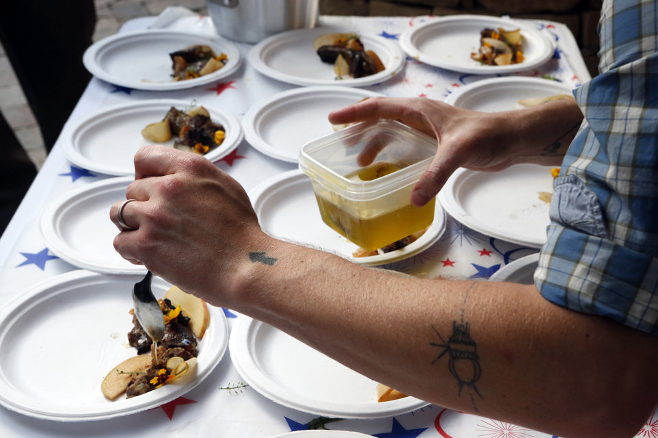 Photo - Below: Open Flame guest chefs Andon Whitehorn and Colin Stringer plate pork ribs on June 12 in Oklahoma City.  Photo by Steve Sisney, The Oklahoman  STEVE SISNEY