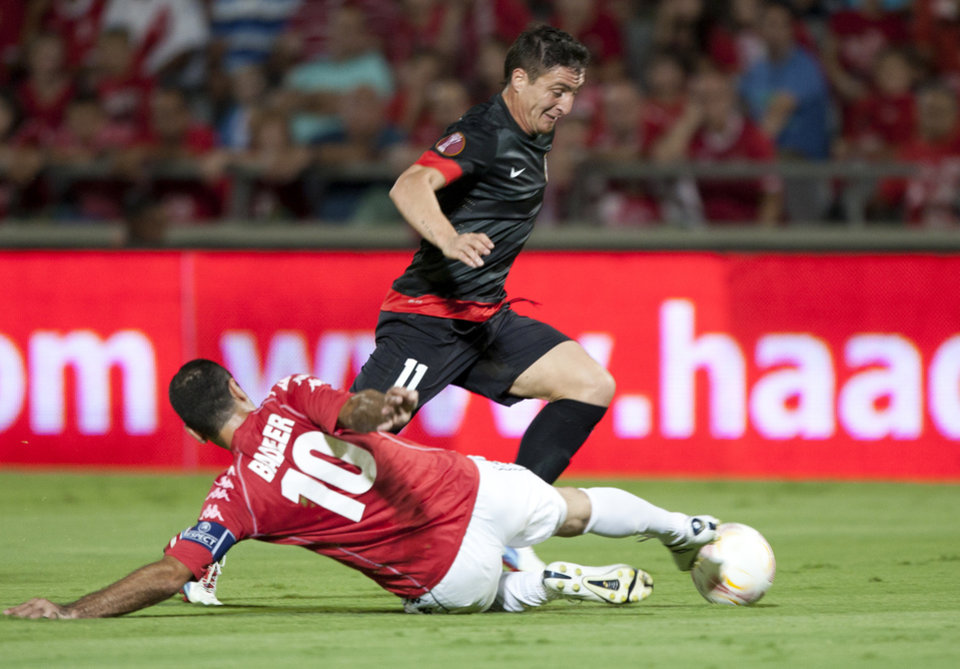 Photo -   Atletico Madrid's Cristian Rodríguez, right, goes past Hapoel Tel Aviv's Walid Badier during their Europa League Group B soccer match at the Bloomfield stadium in Tel Aviv, Israel,Thursday, Sept. 20, 2012. (AP Photo/Ariel Schalit)