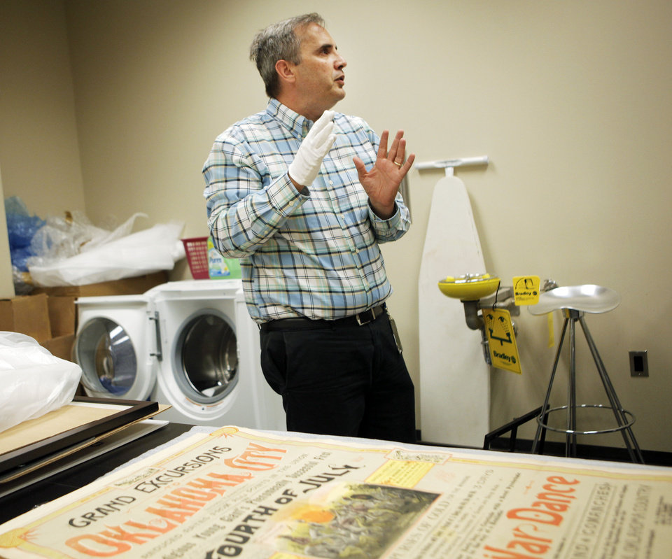 Photo - Oklahoma Historical Society Director of Research Chad Williams explains the details behind the creation of the poster preserved by the century chest from the 1889 4th of July celebration in Oklahoma City. The century chest was a time capsule that was unearthed earlier this year, and contained many items from life in 1913. July 1, 2013 Photo by KT KING, The Oklahoman