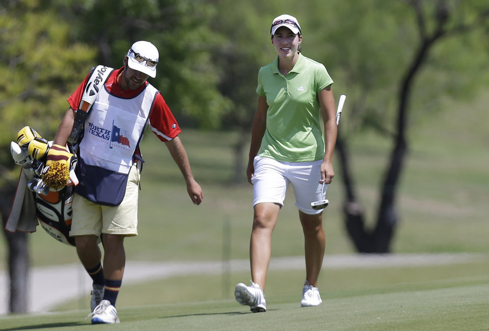 Carlota Ciganda, of Spain, smiles as she walks up on the ninth hole with her caddie during the final round of the North Texas LPGA Shootout golf tournament, Sunday, April 28, 2013, at Los Colinas Country Club in Irving, Texas. (AP Photo/LM Otero)