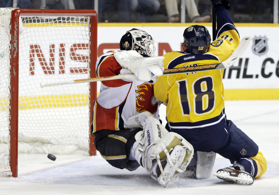 Nashville Predators right wing Brandon Yip (18) collides with Calgary Flames goalie Miikka Kiprusoff, of Finland, as a shot by Nashville Predators\' Nick Spaling, not shown, goes into the net for a goal in the second period of an NHL hockey game, Thursday, March 21, 2013, in Nashville, Tenn. (AP Photo/Mark Humphrey)