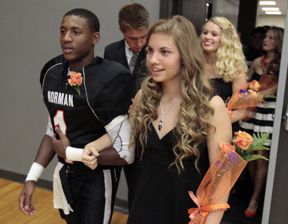 Norman homecoming royalty Sayvon Foley and Christina Ard lead the procession into the gym before the Southmoore/Norman  high school football game on Friday, Oct. 18, 2013 in Norman, Okla.  The coronation was moved inside because of the weather.  Photo by Steve Sisney, The Oklahoman