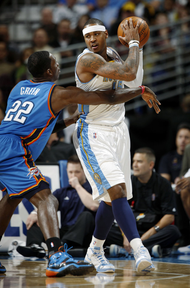 Photo - Denver Nuggets forward Carmelo Anthony, right, looks to pass the ball as Oklahoma City Thunder forward Jeff Green covers in the first quarter of an NBA basketball game in Denver on Monday, Dec. 14, 2009. (AP Photo/David Zalubowski) ORG XMIT: CODZ103