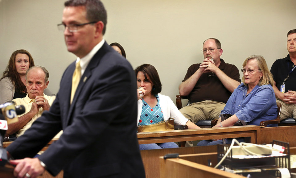 Photo - Three relatives of triple homicide victims sit on the front row of a jury box to hear Stephens County District Attorney Jason Hicks speak on Wednesday, Oct. 15, 2014 to the media about murder charges filed against  University of Oklahoma student Alan Hruby  in the murders of his father, mother and sister. On Monday, the community of Duncan was shocked to learn about the discovery of three members of a prominent Duncan family found dead in their home, victims of a triple homicide in an upscale neighborhood on the north side of town Monday morning,  Oct. 13, 2014.  John and Tinker Hruby and their daughter, Katherine,  17, were found dead by the family's housekeeper.    Photo by Jim Beckel, The Oklahoman