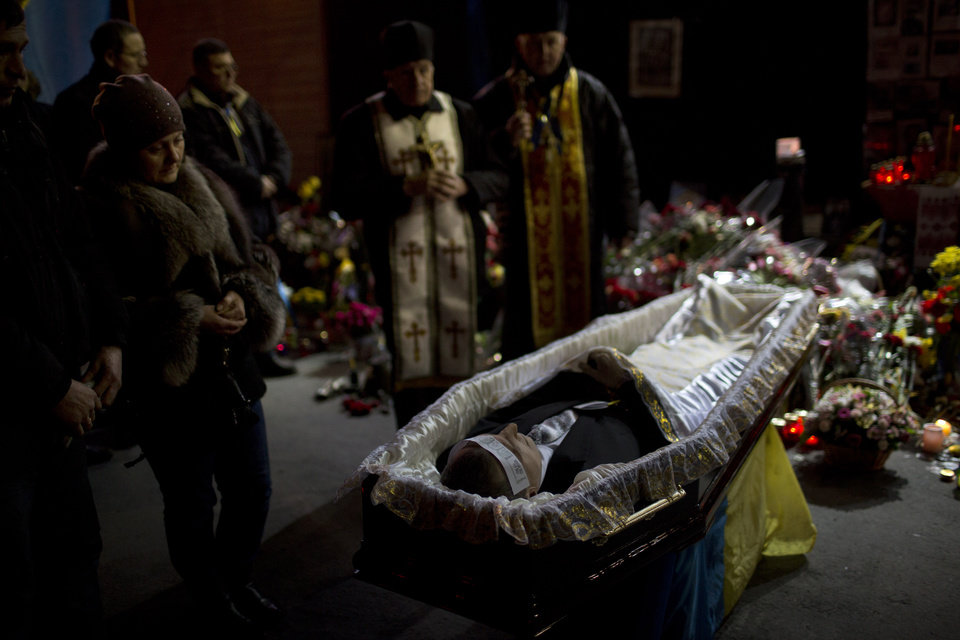 Photo - The body of anti-Yanukovych protester Bailuk Alexander, 40, killed in a recent clash with riot police in Kiev's Independence Square, is seen in a coffin during his funeral on Friday, Feb. 28, 2014, in Ukraine. Official reports say 82 people were killed in severe clashes between opposition activists and riot police. (AP Photo/Emilio Morenatti)