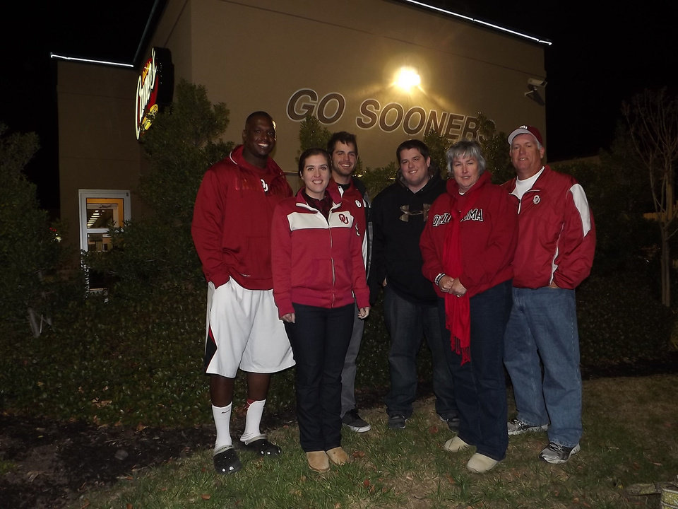 Photo - Above: OU defensive end David King, left, with the McVaneys (from left): Katie, Jeff, Tom, Stacy and John. King's life was changed because of two mothers — one who steered him away from the streets and the other who kept a promise.