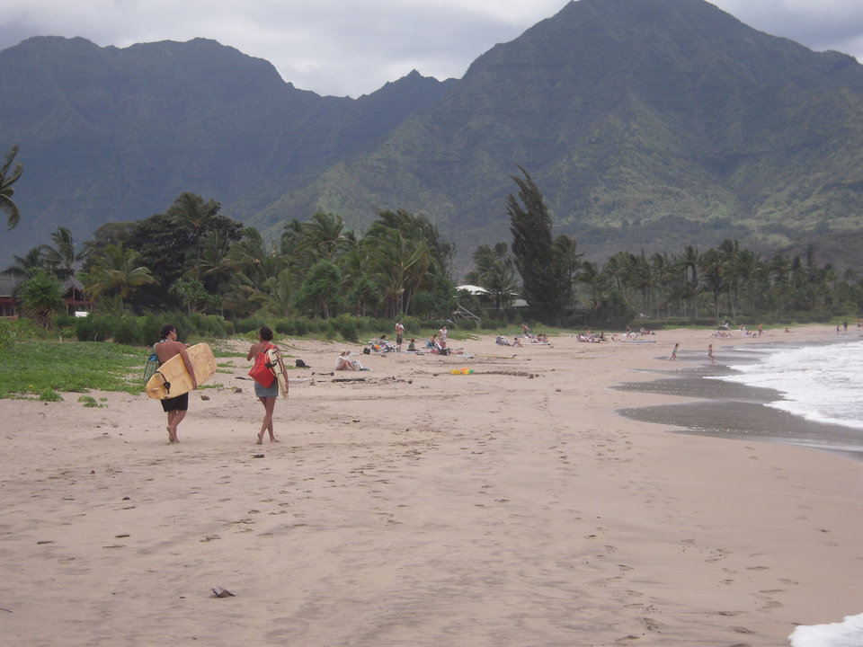 "Surfers head home after spending the day at Hanalei Bay in Hanalei, Hawaii. Hanalei Bay was named the nation's No. 1 beach in ""Dr. Beach"" Stephen P. Leatherman's annual rankings. (AP PHOTO)"