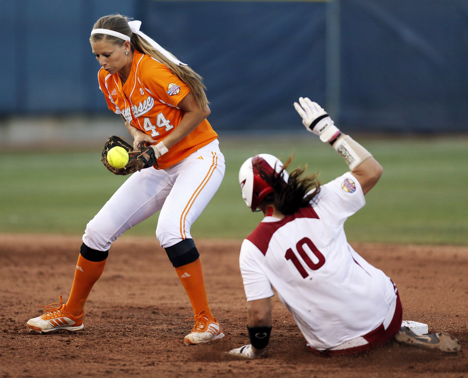 Photo - OU's Keilani Ricketts (10) makes it safely to second base as Tennessee's Madison Shipman (44) tries to control the ball in the fourth inning during Game 1 of the Women's College World Series NCAA softball championship series between Oklahoma and Tennessee at ASA Hall of Fame Stadium in Oklahoma City, Monday, June 3, 2013. Photo by Nate Billings, The Oklahoman