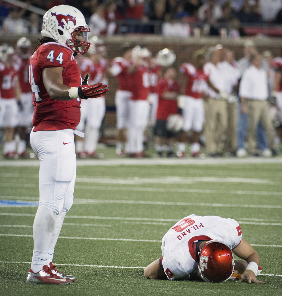 Photo -   SMU linebacker Taylor Reed stands next to Houston quarterback David Piland (8) after his late hit knocked Piland out of the game during the second quarter of an NCAA college football game Thursday, Oct. 18, 2012, in Dallas. Reed was flagged for a personal foul penalty on the play, which was declined in favor of a defensive pass interference call. (AP Photo/Houston Chronicle, Smiley N. Pool) MANDATORY CREDIT