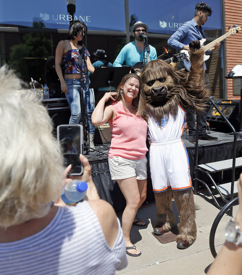 Photo -  Patricia Willson has her picture taken with Rumble the Bison during Wednesday's Allied Arts' Brackets for Good Championship Celebration in Automobile Alley. [PHOTO BY NATE BILLINGS]