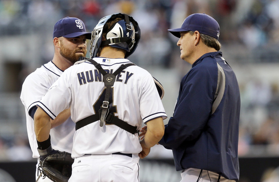 Photo - San Diego Padres starter Sean O'Sullivan, left, gets a visit from pitching coach Darren Balsley, right, and catcher Nick Hundley during a first inning jam against the Cincinnati Reds in a baseball game in San Diego, Monday, July 29, 2013. (AP Photo/Lenny Ignelzi)