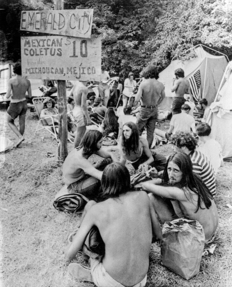 "FILE - In this Aug. 1, 1970, file photo, youths sell marijuana openly from sacks at a banned music festival in Middlefield, Conn. beneath a sign advertising their products as ""Mexican Coletus at $10 an ounce.""As the conformity of the postwar era took hold, getting high on marijuana and other drugs emerged as a symbol of the counterculture, with Jack Kerouac and the rest of the Beat Generation singing pot's praises. On the occasion of  �Legalization Day,� Thursday, Dec. 6, 2012, when Washington�s new law takes effect, AP takes a look back at the cultural and legal status of the �evil weed� in American history. (AP Photo/File)"