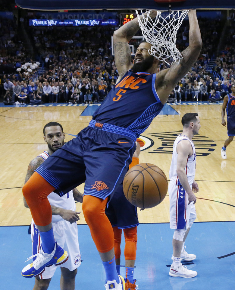 Photo - Oklahoma City Thunder forward Markieff Morris hangs from the basket after a dunk during the first half of the team's NBA basketball game against the Philadelphia 76ers on Thursday, Feb. 28, 2019, in Oklahoma City. (AP Photo/Sue Ogrocki)