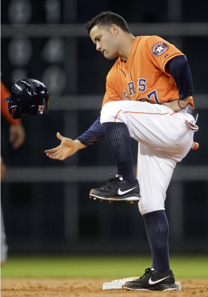 Photo - Houston Astros' Jose Altuve kicks his helmet after having a steal at second overturned for an out after video review, during the sixth inning of a baseball game against the Miami Marlins, Friday, July 25, 2014, in Houston. (AP Photo/Patric Schneider)
