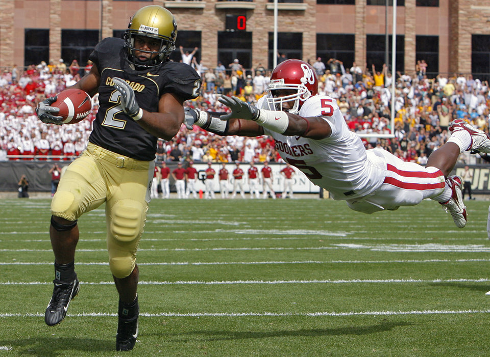 Photo - Oklahoma's Nic Harris (5) dives to try and bring down Colorado's Hugh Charles (2) who runs into the end zone for a touchdown during the first half of the college football game between the University of Oklahoma Sooners (OU) and the University of Colorado Buffaloes (CU) at Folsom Field on Saturday, Sept. 29, 2007, in Boulder, Co.   By CHRIS LANDSBERGER, The Oklahoman  ORG XMIT: KOD