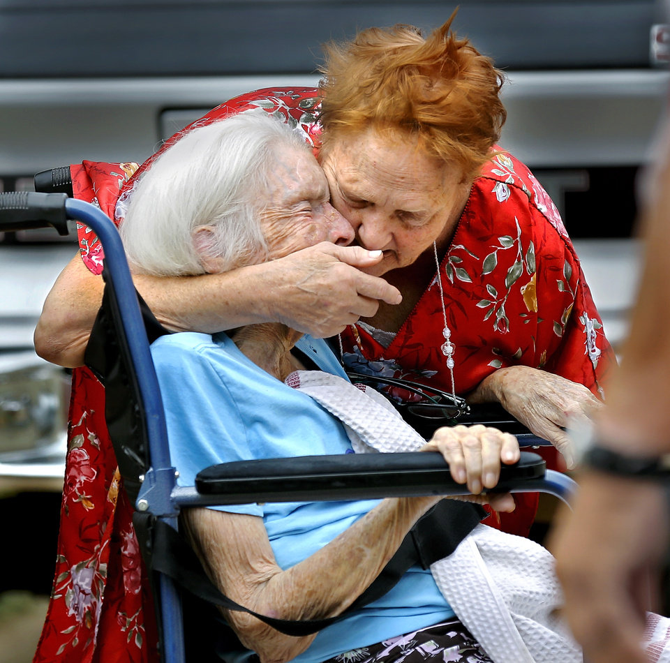 Photo - An elderly woman who was rescued from a burning trailer house is comforted by a neighbor as paramedics arrive to attend to her. The woman was treated at the scene and was taken to the manager's office. A blaze destroyed a trailer in the Skyline Mobile Home Park on E. Reno and Eastbrook Terrace in Del City on Thursday, June 26, 2014. Del City firefighters put out the fire before it could spread to adjoining properties. The park manager joined neighbors in helping two women and a dog escape from the flames. Theyran to the trailer and  pulled a middle-aged woman and her elderly mother, who is confined to a wheelchair, from the home as flames leaped from windows and the roof and dark gray smoke rose into the air. A pet dog was saved but another dog perished in the fire.  Photo by Jim Beckel, The Oklahoman