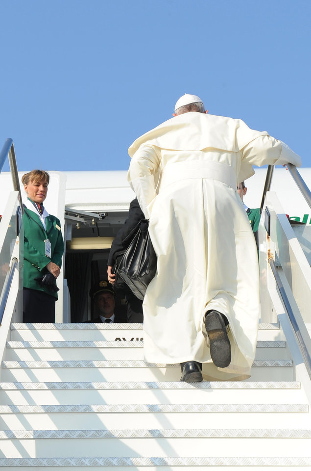 Photo - In this photo provided by the Vatican newspaper L'Osservatore Romano, Pope Francis holds a bag as he boards a plane at Rome's Leonardo Da Vinci international airport, Monday, July 22, 2013. It's wheels up on Pope Francis' first trip abroad as pontiff. A special Alitalia flight carrying Francis, his entourage and journalists who will cover him on his week-long visit to Brazil took off 10 minutes behind schedule Monday from Rome's Leonardo da Vinci airport. Keeping to his example that the Catholic church must be humble, Francis carried his own black hand luggage. He even kept holding it with his left hand while he used his left to shake hands with some of the VIPs who turned out to wish him well and while he climbed the stairs to the jet's entrance. Among the dignitaries was Italian Premier Enrico Letta. (AP Photo/L'Osservatore Romano, ho)