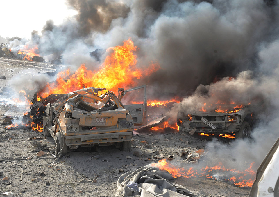In this photo released by the Syrian official news agency SANA, flames and smoke raise from burned cars after two bombs exploded, at Qazaz neighborhood in Damascus, Syria, on Thursday May 10, 2012. Two large explosions ripped through the Syrian capital Thursday, heavily damaging a military intelligence building and leaving blood and human remains in the streets. (AP Photo/SANA) ORG XMIT: BEI108