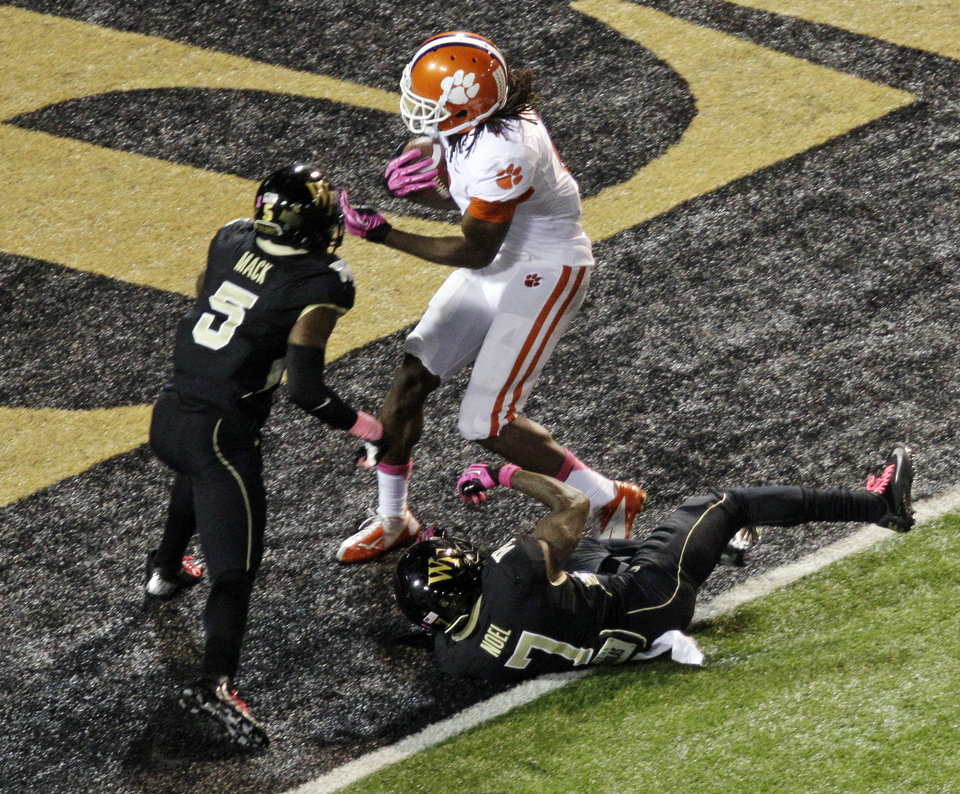 Clemson\'s DeAndre Hopkins, right, catches a touchdown pass as Wake Forest\'s Daniel Mack, left, and Merrill Noel, bottom, defend during the first half of an NCAA college football game in Winston-Salem, N.C., Thursday, Oct. 25, 2012. (AP Photo/Chuck Burton)