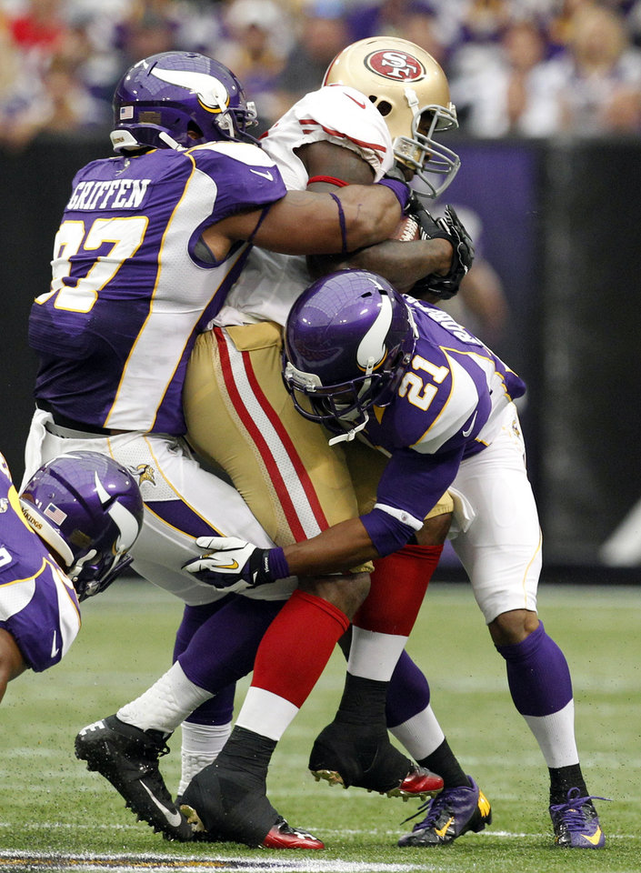 Photo -   San Francisco 49ers tight end Vernon Davis, center, is tackled by Minnesota Vikings defensive end Everson Griffen, left, and cornerback Josh Robinson, right, after making a reception during the first half of an NFL football game Sunday, Sept. 23, 2012, in Minneapolis. (AP Photo/Genevieve Ross)