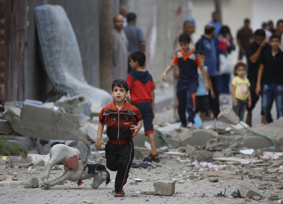 Photo - A Palestinian child runs on debris from a destroyed house, following an overnight Israeli strike in Beit Lahiya, in northern Gaza strip, Saturday, July 19, 2014. A Gaza health official says the death toll from Israel's 12-day offensive against Hamas militants has topped 300. (AP Photo/Lefteris Pitarakis)