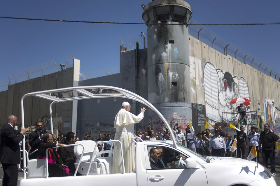 Photo - Pope Francis waves as he rides on a vehicle passing by Israel's separation barrier on his way to a mass in Manger Square next to the Church of the Nativity, traditionally believed to be the birthplace of Jesus Christ in the West Bank town of Bethlehem on Sunday, May 25, 2014. Francis called the Israeli-Palestinian stalemate