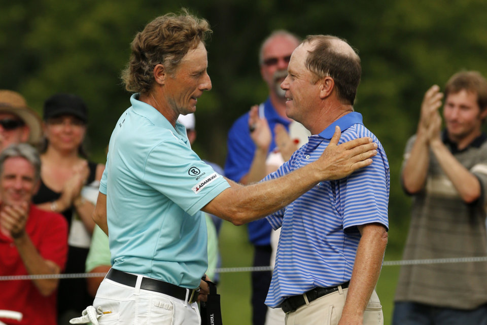 Photo - Bernhard Langer of Munich, Germany, left, is congratulated by Jeff Sluman after sinking a birdie putt on the 18th green on the second hole of a sudden death playoff with Sluman to win the Senior Players Championship golf tournament at Fox Chapel Golf Club in Pittsburgh, Sunday, June 29, 2014. (AP Photo/Gene J. Puskar)