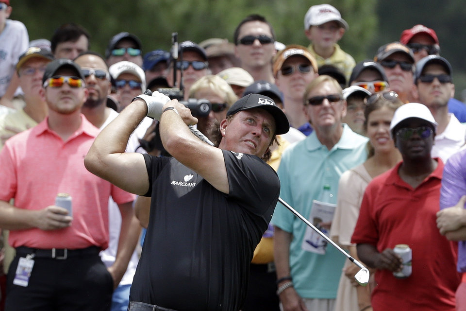 Photo - Phil Mickelson hits on the 17th fairway during the second round of the St. Jude Classic golf tournament Saturday, June 7, 2014, in Memphis, Tenn. Mickelson shot a par on the hole. Bad weather on Friday caused the second round to continue into Saturday. (AP Photo/Mark Humphrey)