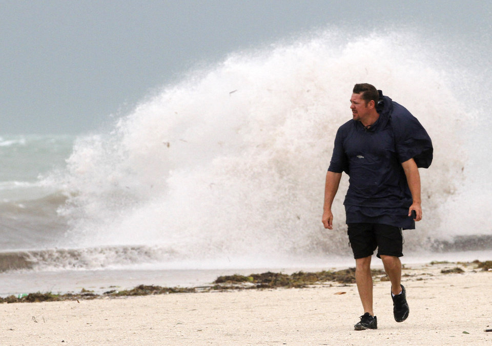 Photo - A man walks on the beach in Key West, Fla., Sunday, Aug. 26, 2012 as heavy winds hit the northern coast from Tropical Storm Isaac. Isaac is expected to continue streaming across Marion County Monday as it continues toward the northern Gulf of Mexico. National Weather Service officials in Jacksonville on Sunday said Marion County began getting rain bands from Isaac around 2 p.m. and that the rain would continue through Tuesday. (AP Photo/Alan Diaz) ORG XMIT: FLAD108